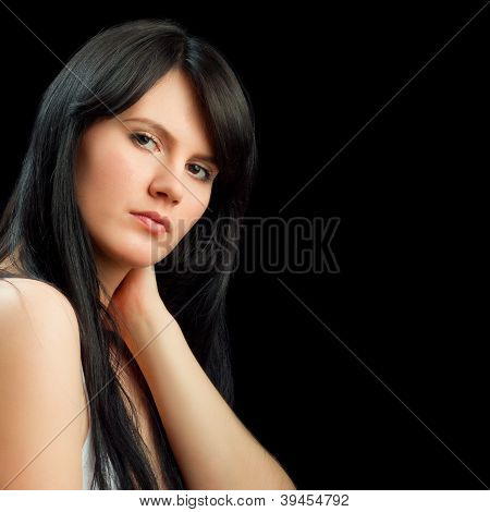 Portrait Of A Beautiful Young Woman Holding Her Neck Isolated On Black