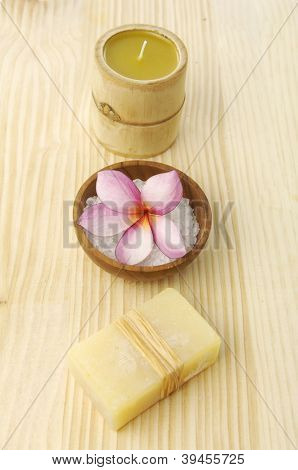 Set of handmade soaps, candle, frangipani,salt in bowl on wooden board