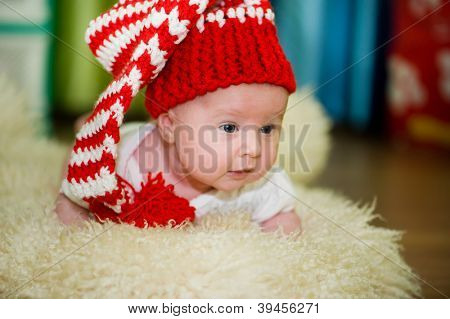 baby  girl lying in a red hat