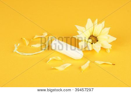 cotton tampon with yellow flower on orange background close-up