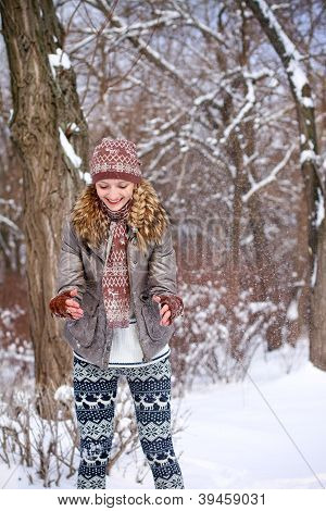 Happy Young Woman Playing With Snow Outdoors