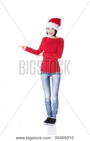 Beautiful smiling christmas santa woman pointing on side showing copyspace. Isolated on white background.