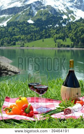 Wine and vegetables served at picnic on Alpine meadow. Switzerland