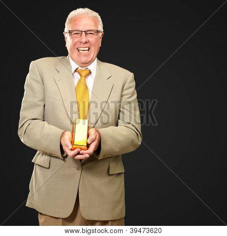 Senior Man Holding Gold Bar On Black Background