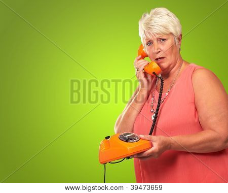 Portrait Of A Senior Woman Holding A Retro Phone On Green Background