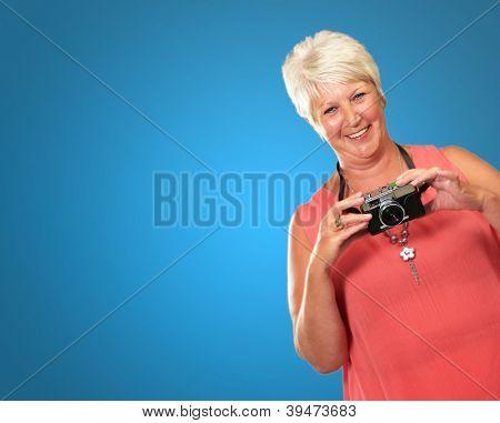 Senior Woman Holding Camera Isolated On Blue Background