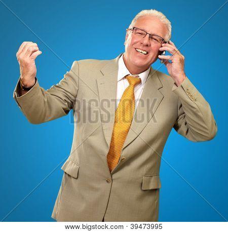 Senior Business Man Talking On Phone Isolated On Blue Background