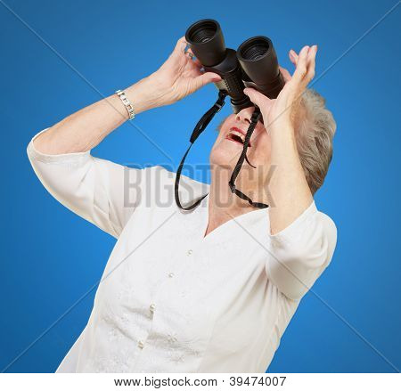 portrait of senior woman looking through a binoculars over blue background