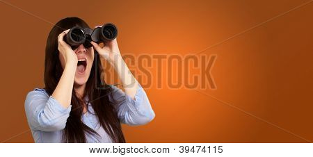 Portrait Of A Young Woman Looking Through Binoculars On Orange Background