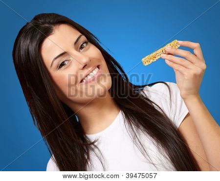 portrait of young woman eating cereal bar over blue background