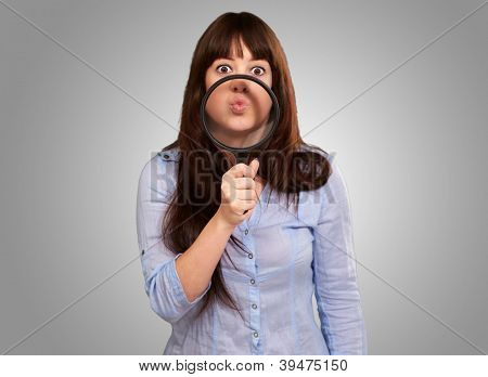 Woman Holding Magnifying Glass On Mouth Isolated On Grey Background