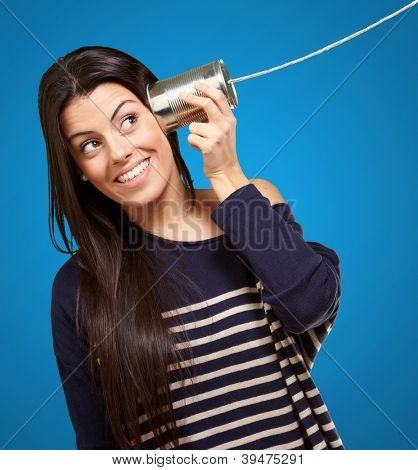 Young woman hearing using a metal tin can over blue background