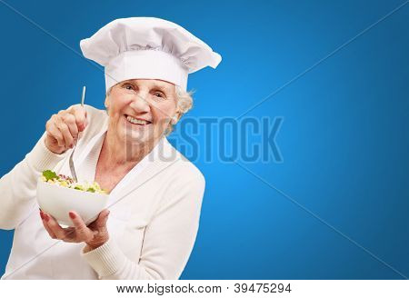 portrait of adorable senior cook woman eating salad against a blue background