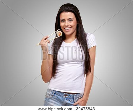 Portrait Of A Female Holding A Maki Sushi On Gray Background