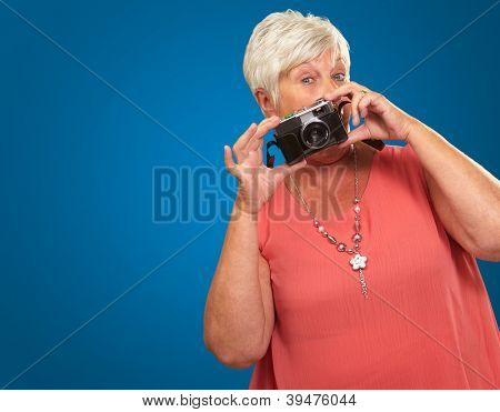 Senior Woman Holding Camera Isolated On Blue Background