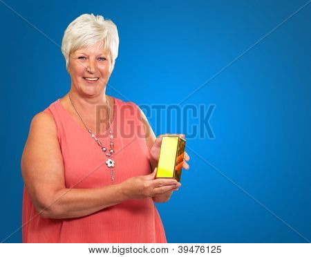 Senior Woman Holding a golden bar Isolated On Blue Background