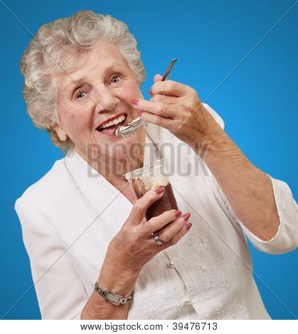 portrait of senior woman eating chocolate and cream cup over blue
