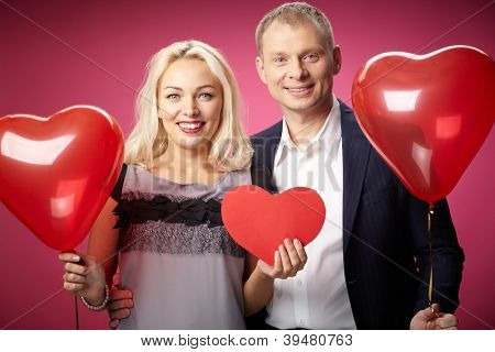 Portrait of happy couple with red paper heart and heart-shaped balloons looking at camera