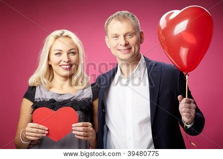 Portrait of happy couple with red paper heart and heart-shaped balloon looking at camera
