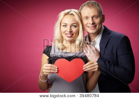 Portrait of happy couple with red paper heart looking at camera