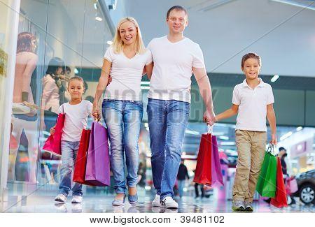 Retrato de família moderna com paperbags andando no shopping
