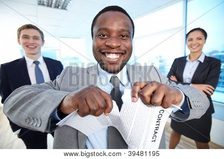 Portrait of happy African businessman tearing contract while looking at camera with two partners near by