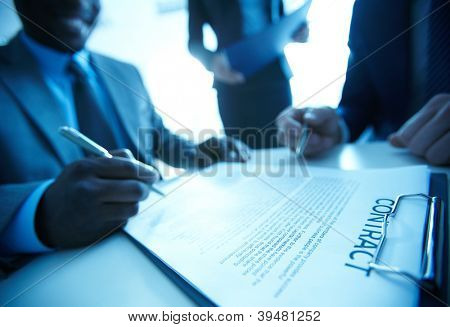 Image of businessman signing contract with two employees near by
