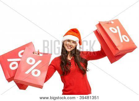 Menina feliz em cap Santa detém paperbags vermelho com símbolo de desconto