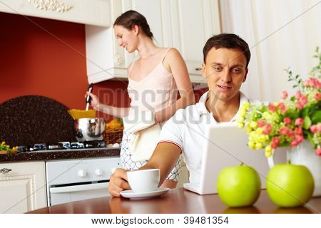 Portrait of handsome man looking at laptop display in the kitchen with his wife cooking on background
