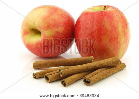 dried cinnamon sticks and fresh apples on a white background