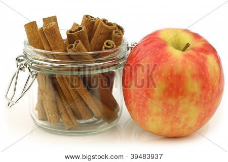dried cinnamon sticks in a glass jar and a fresh apple on a white background