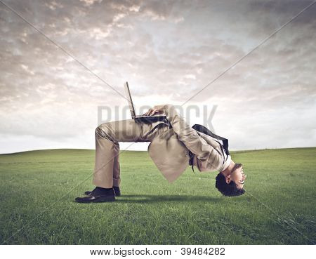 A man gets upside down while using a computer in a large field