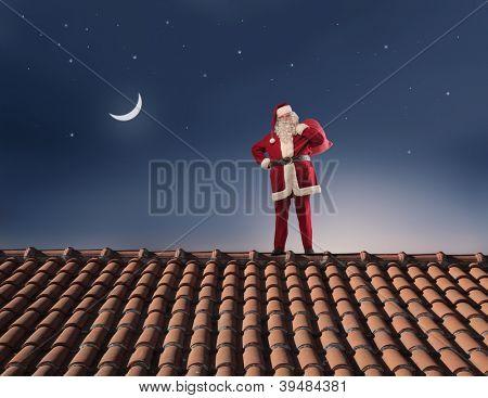 Papai Noel no telhado de uma casa com seu saco cheio de presentes