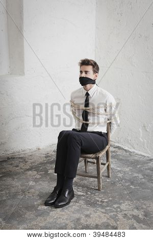 Young businessman tied to a chair in a basement