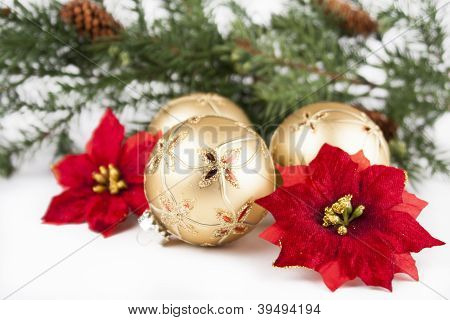 Christmas ornaments and poinsettia flowers with pine greens on white