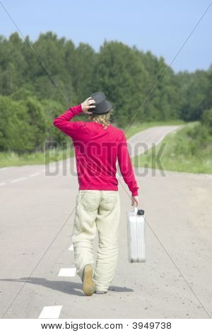 Young Man Walking Down Highway With Empty Gas Can