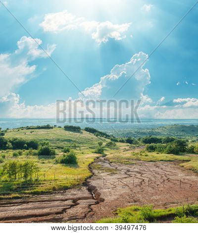 blue sky with clouds and sun over drought earth in mountains