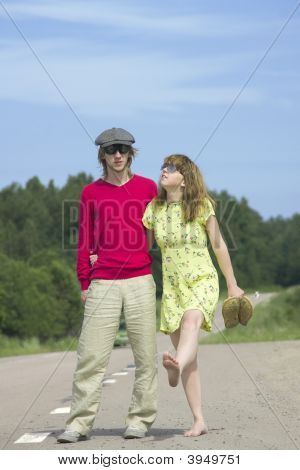 The Young Couple Walks On The Highway