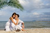 stock photo of loving_couple  - happy loving couple hugging on beach on summer honeymoon vacation - JPG