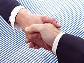 stock photo of soliciting  - Conceptual photography of a business handshake on a blue background - JPG