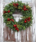 Christmas wreath on a rustic wooden front door.