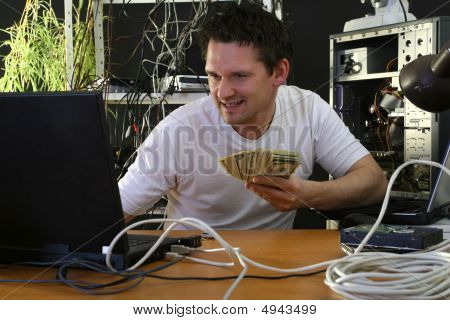 Man With Money Working On Computer