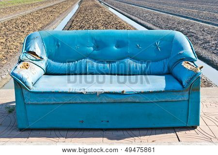 Very Old Vintage Blue Sofa On The Street