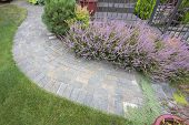 foto of red siding  - Front Yard Garden Curve Brick Paver Path with Green Grass Lawn Flowering Plants Trees and Shrubs Top View - JPG