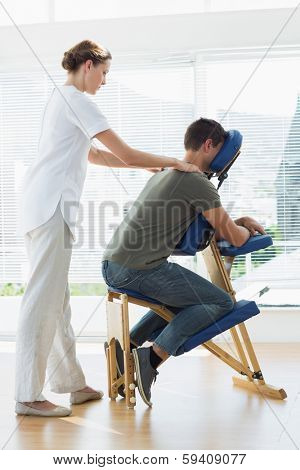 Full length of man receiving shoulder massage from therapist in hospital