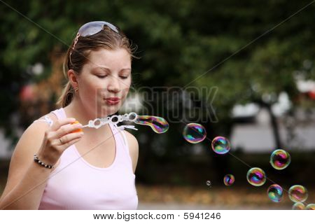 Young Woman Blows Bubbles