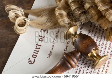 Hammer and judge's wig lying on a court's judgment text