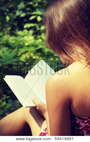 Reading woman sitting in a park bench in summer.