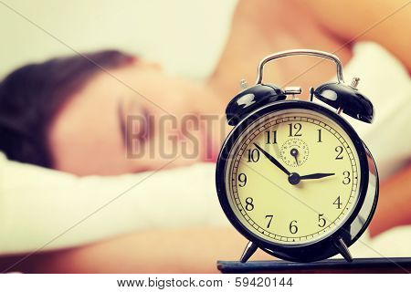 Woman in bed trying to wake up with alarm clock