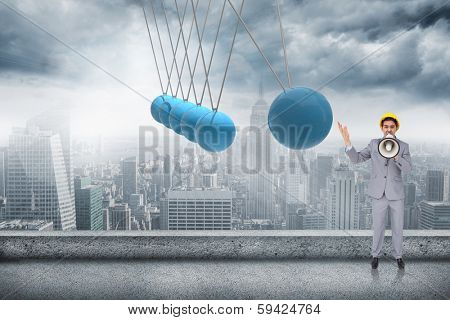 Architect with hard hat shouting with a megaphone against newtons cradle above city